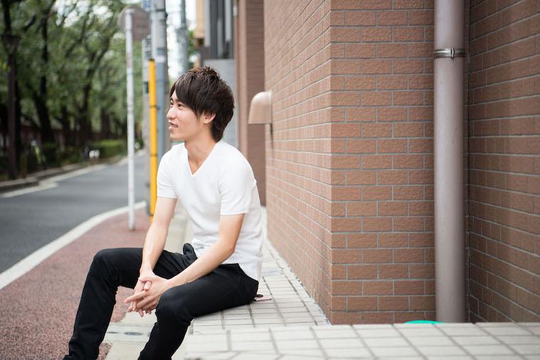 【写真】街頭で座り、笑顔でどこかをみつめるかないしゅんさん