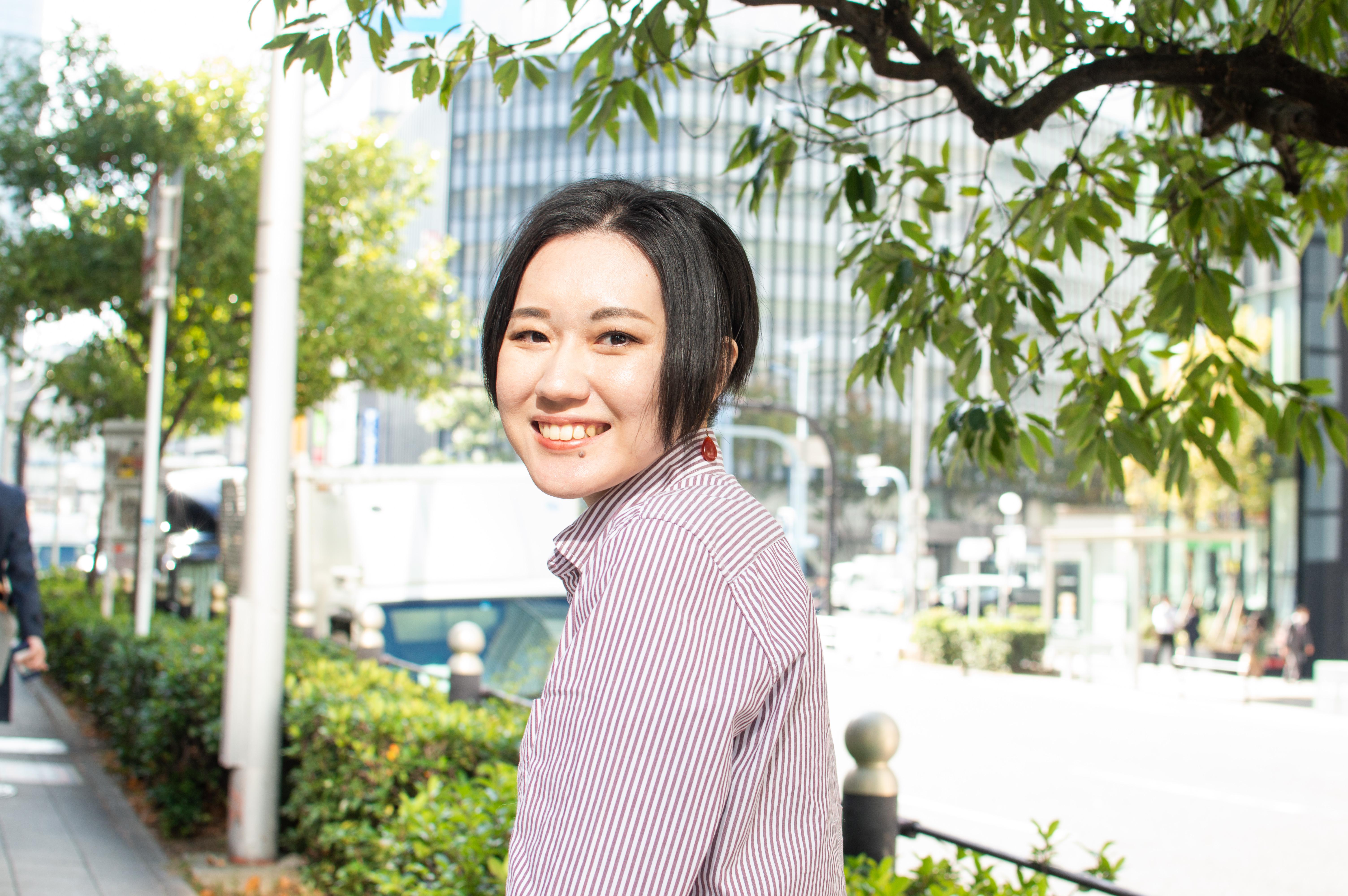 【写真】街頭で満面の笑みをみせるみやざきあすかさん