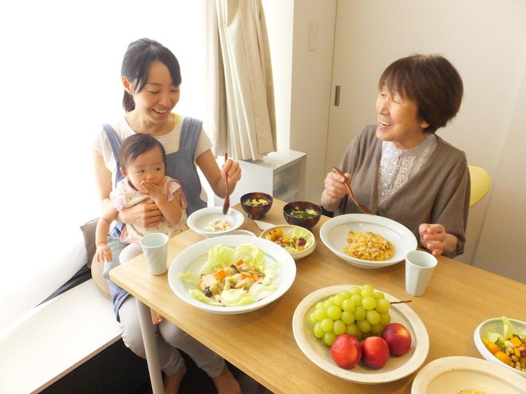 【写真】てまるのお皿、スプーンを使って食事をする笑顔の高齢者と赤ちゃんを抱く女性