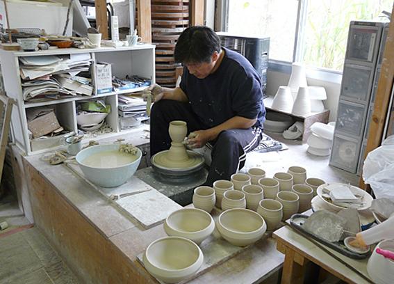 【写真】工房で陶器をつくるおおさわかずよしさん