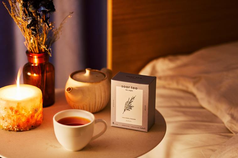 【写真】ベッドのサイドテーブルにキャンドルや雑貨と共に置かれるsoar teaとマグカップ