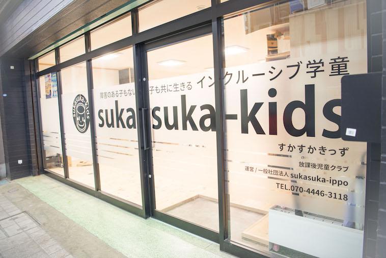 【写真】すかすかきっずの入り口。ガラス扉に「障害のある子もない子も共に生きるインクルーシブ学童」と記載。