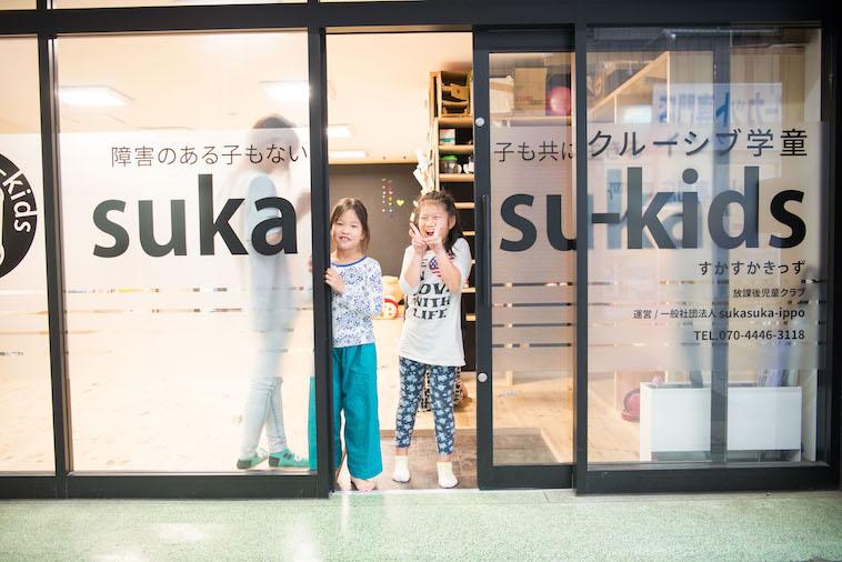 【写真】こどもたちが、入り口から笑顔で外をのぞいている。