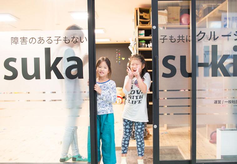 【写真】すかすかきっずに通う小学生の子どもたちが、教室の入り口から笑顔で外をのぞいている。