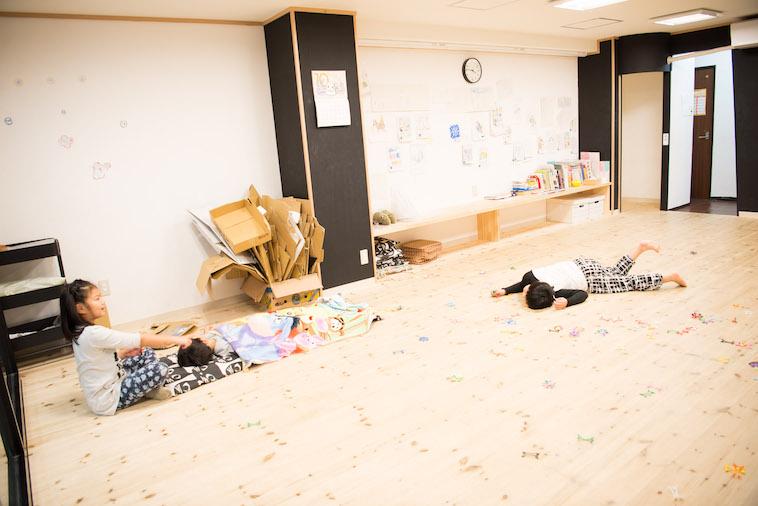 【写真】無垢の床に寝転んでいるこどもたち。居心地がよさそうだ。