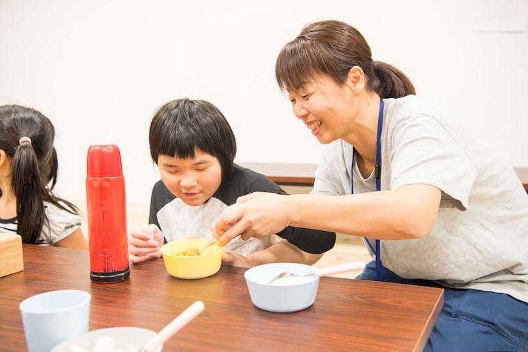 【写真】現場リーダーのよしだやえこさん、こどもと一緒にスプーンを握り、ご飯の食べ方を教えている。とても楽しそうだ。