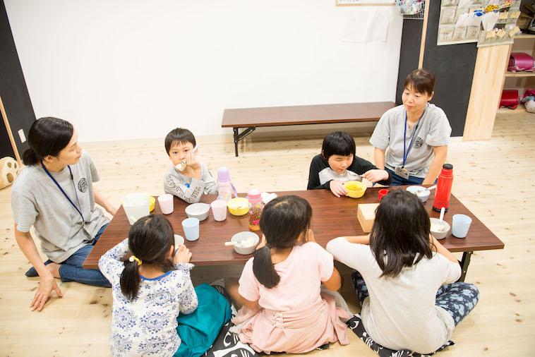 【写真】こどもたちとスタッフが一つのテーブルを囲いおやつを食べている。それぞれ居心地がよさそうだ。