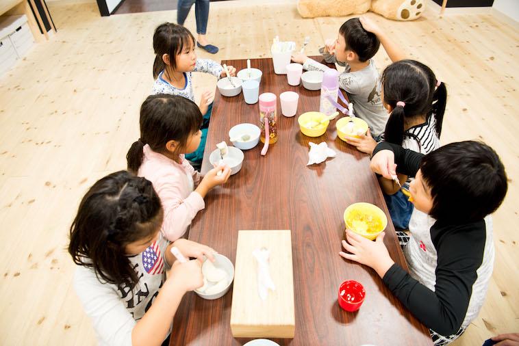 【写真】ひとつのテーブルを囲みおやつを食べているこどもたち。夢中でおやつを頬張っている。