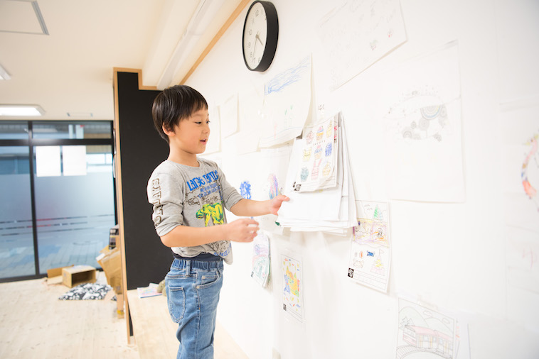【写真】壁に貼ってある絵について解説をしてくれるこども。いきいきとしている。