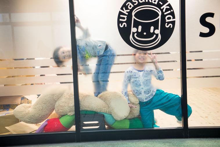 【写真】すかすかきっずの入り口のガラス戸から外をのぞくこどもたち。