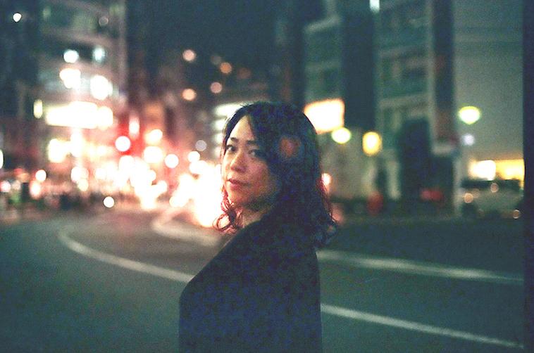 【写真】夜の街に笑顔で立っているなかむらすえこさん
