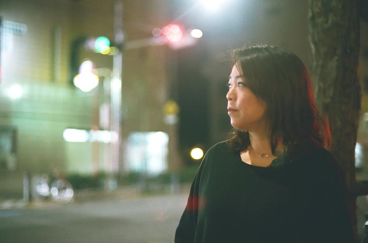 【写真】夜の街で遠くを見つめるなかむらすえこさん