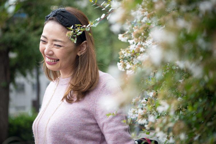 【写真】花の前で笑顔でうつるうめつえりさん