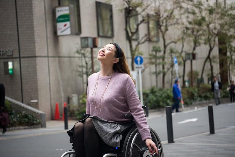 【写真】街頭で車椅子に座り空を清々しい表情でみつめるうめつえりさん