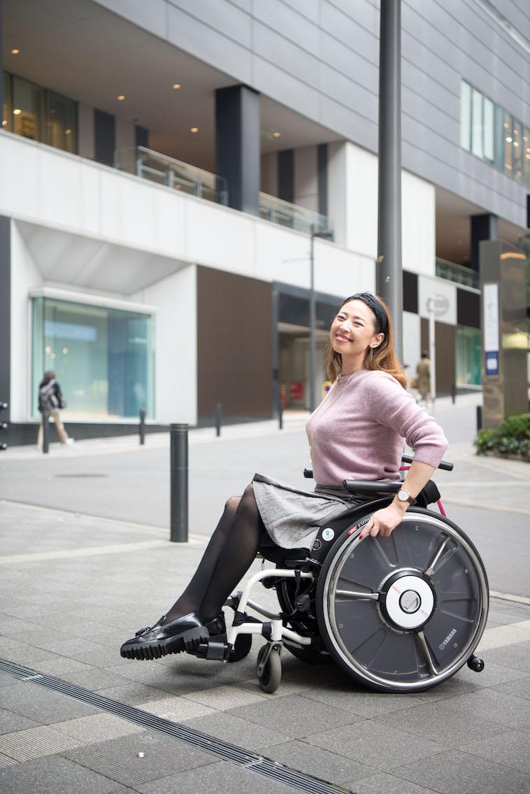 【写真】街頭をほほえみながら車椅子で移動するうめつえりさん