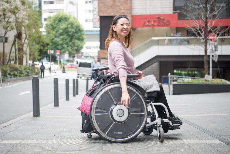 【写真】街頭で車椅子を笑顔で移動するうめつえりさん