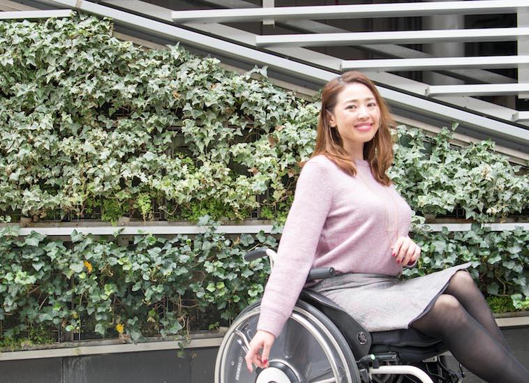【写真】街頭で笑顔で車椅子に座っているうめつえりさん