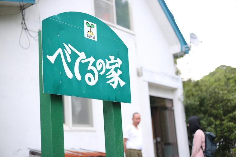 【写真】べてるの家の玄関前。ボードには大きく「べてるの家」と描かれている。