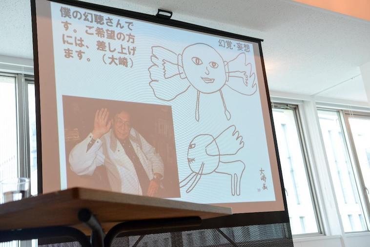 【写真】イベントでプロジェクターにうつされたスライド。 「僕の幻聴さんです。ご希望の方には差し上げます。(大崎)」という文字の横に、人の顔のようなものから羽がはえたキャラクターの絵が描かれている。