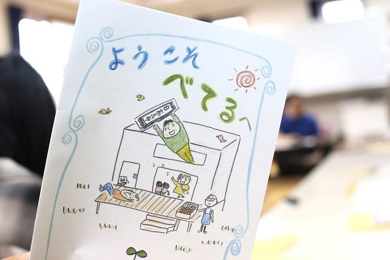 【写真】べてるの家のパンフレット。ようこそべてるへ、という文字の下にはかわいらしいイラストが描かれている