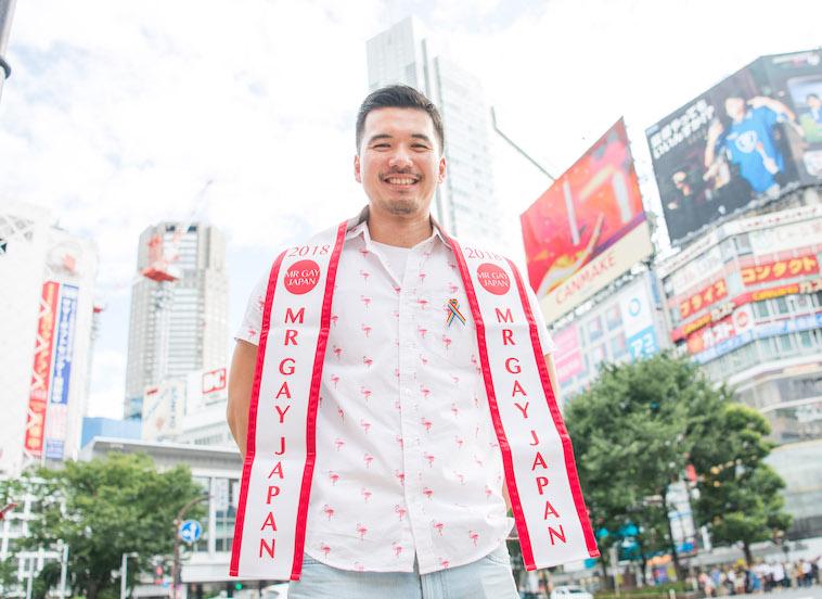 【写真】人の多い街頭で笑顔で立っているしょうごさん。首から、「2018 ミスターゲイジャパン」と書かれたたすきをかけている。