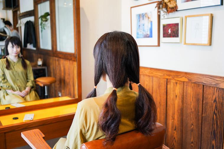 【写真】カット前に、髪の毛を4つの束に結び準備をする
