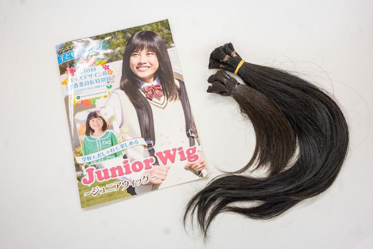 【写真】子ども向けウィッグのパンフレットと、ドネーションされた髪の毛の束