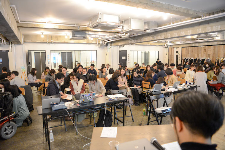 【写真】満員の会場。参加者たちはグループにわかれ、それぞれ楽しそうな様子で話している。