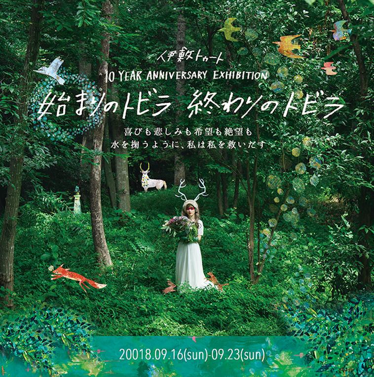 【写真】個展「始まりのトビラ 終わりのトビラ」のポスター。森の中心にいしきさんがいる。その周りには、いしきさんが描いた動物のイラストがいたる所に描かれている。