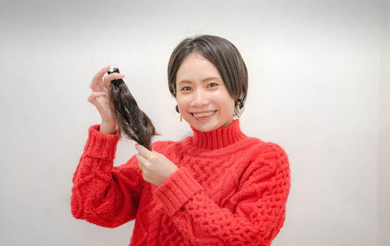 【写真】カットした髪の毛を持ってほほえむsoar代表のくどうみずほ