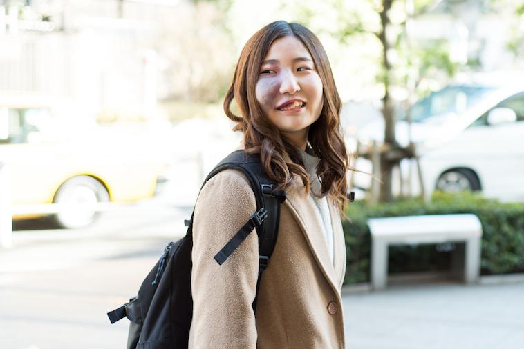 【写真】笑顔で街頭を歩くあやさん