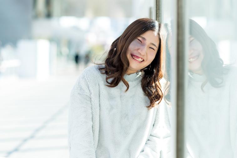 【写真】外がみえる窓によりかかり、満面の笑顔をみせるあやさん