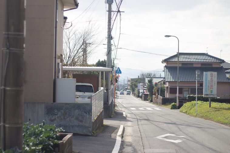 【写真】学園の近くにある道路。複数の一軒家があり、そこで暮らしている人がいるとわかる。
