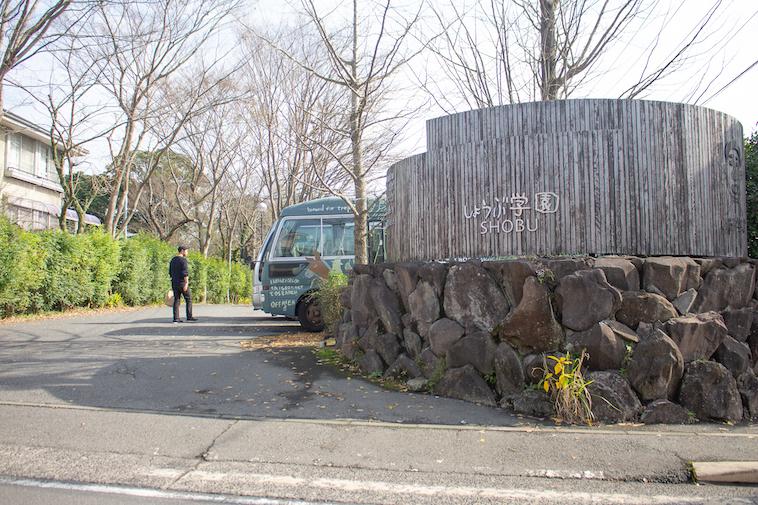 【写真】しょうぶ学園の入り口。木製の壁に素朴な形で「しょうぶ学園」書かれている。