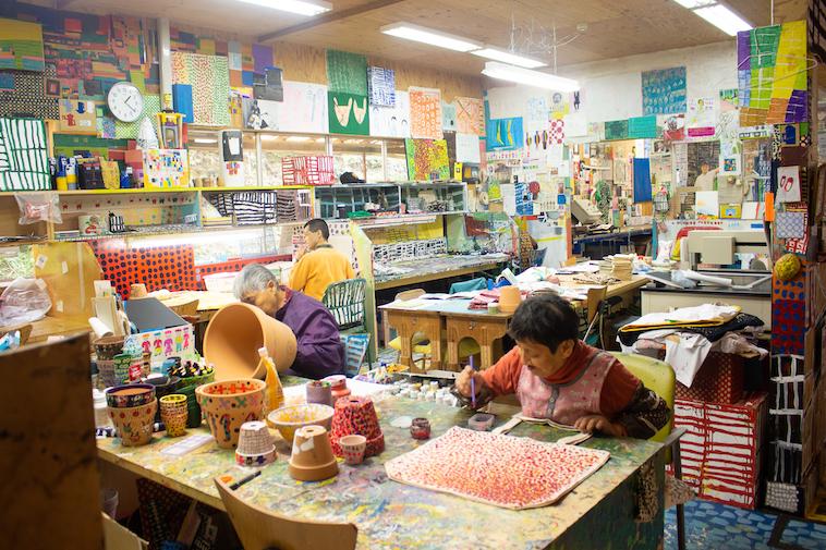 【写真】学園内にあるアトリエ。壁中に利用者が作った作品が飾ってある。そのなかで椅子に座って絵具を持ち黙々と作業している。