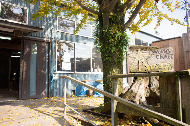 【写真】こうぼうしょうぶアトリエの入り口。木製の看板に「木の工房」とほられている。