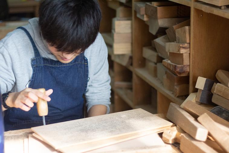 【写真】木製の板を彫刻刀でたたく利用者。楽しそうだ。