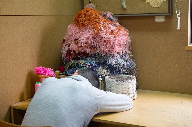 【写真】休憩がてら机に突っ伏している利用者。自分の感覚を大切にしながら休憩をとっている。