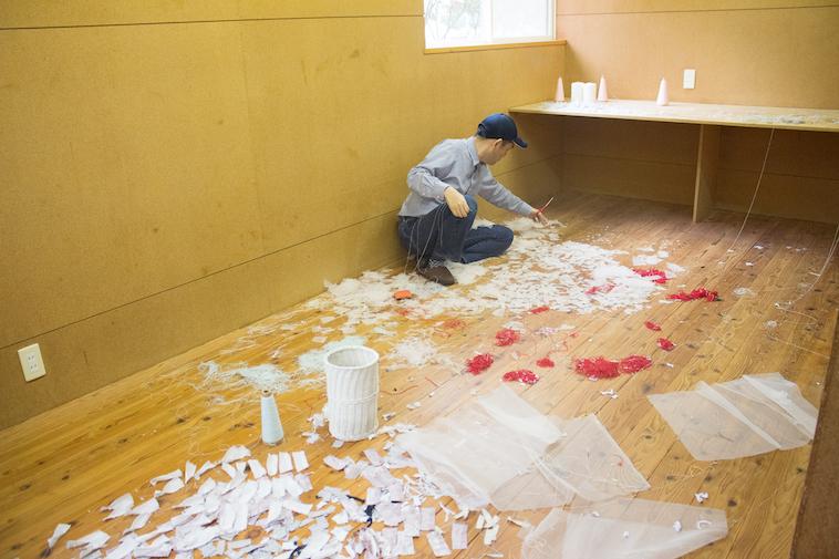 【写真】施設に床に破いた紙をばらまき、作品を作っている利用者。