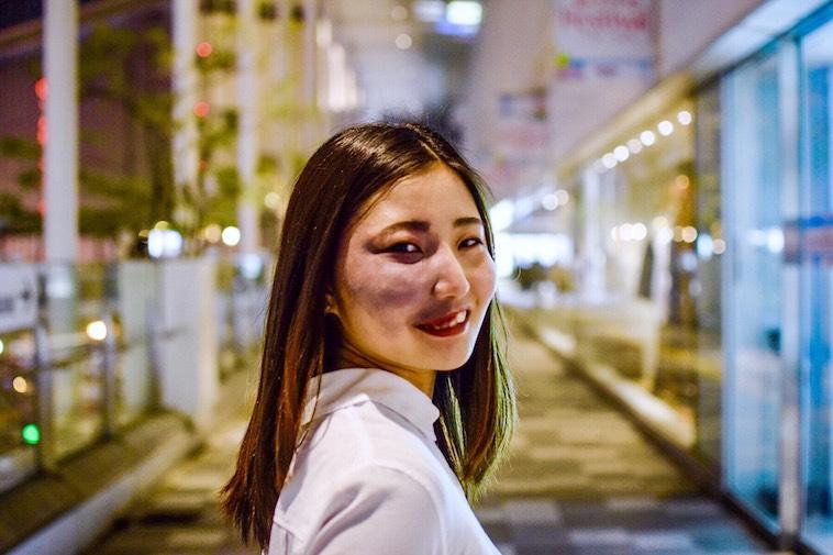 【写真】街頭で後ろを振り返り笑顔をみせるあやさん