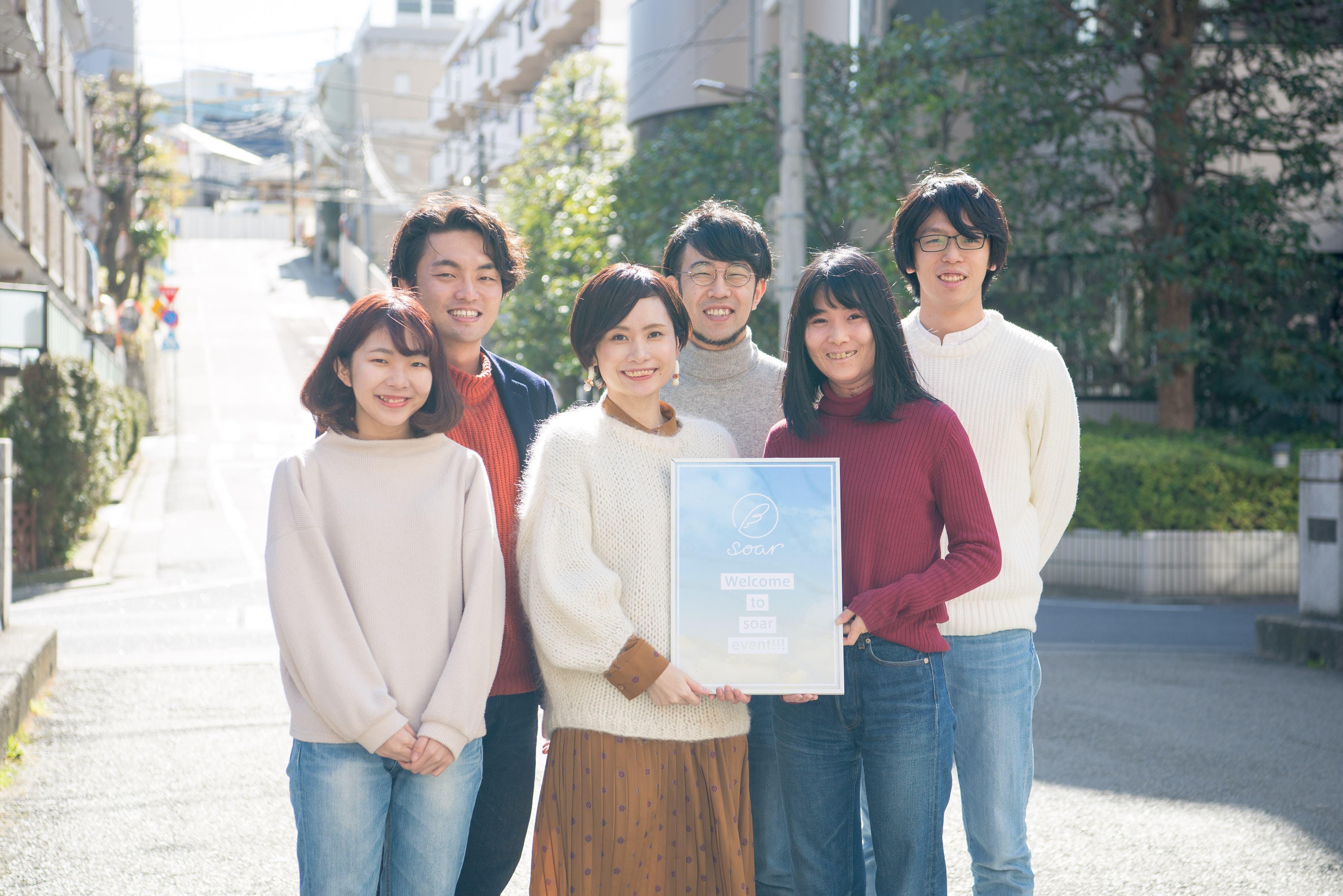 【写真】晴れた日に屋外でsoarのロゴが入ったポスターを持って微笑むメンバーの集合写真