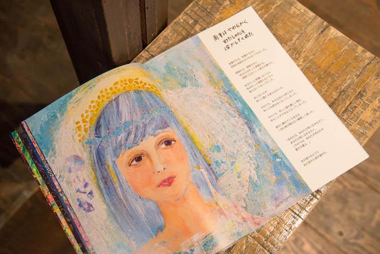 【写真】画集の一部。女性のイラストが見開き2ページで描かれていて、その横に「雨音はやわらかくわたしの心を溶かしてくれた」と書かれている。温かい雰囲気が伝わってくる