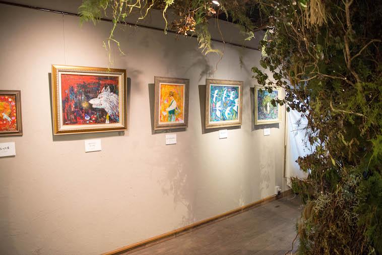 【写真】いしきさんの作品が展示されている。その前には木を連想させる会場装飾がある