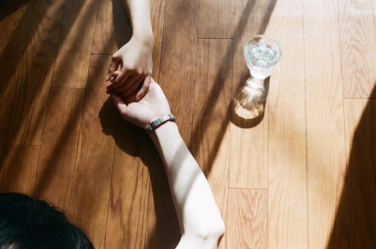 【写真】光が差し込む床には、水の入ったコップが一つが置かれている。その隣では、誰かが手をつないでいる。