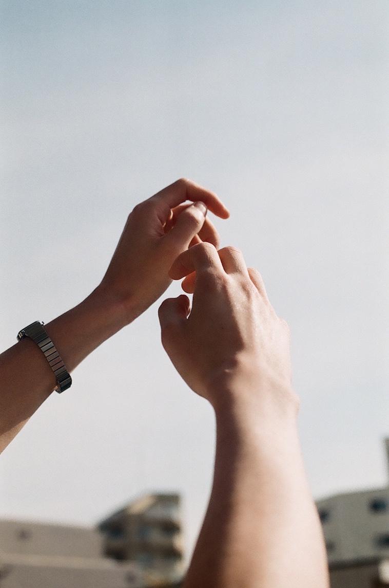 【写真】空に向かって伸ばしている誰かの両手がうつっている