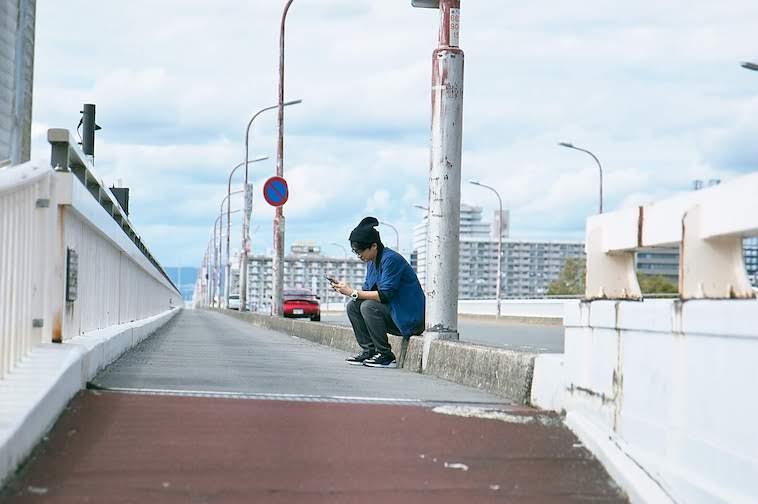 【写真】外で座りながら携帯を使用しているかないつかさん