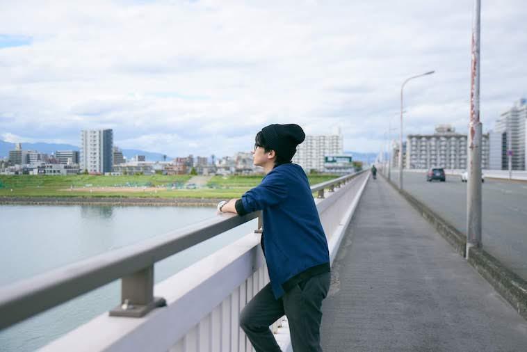 【写真】橋からどこかを眺めるかないつかさん