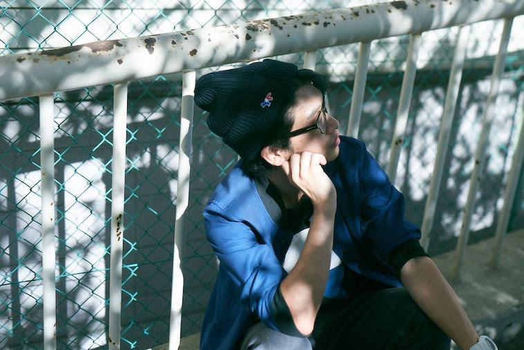 【写真】手すりの前に座り、どこかをみつめるかないつかさん