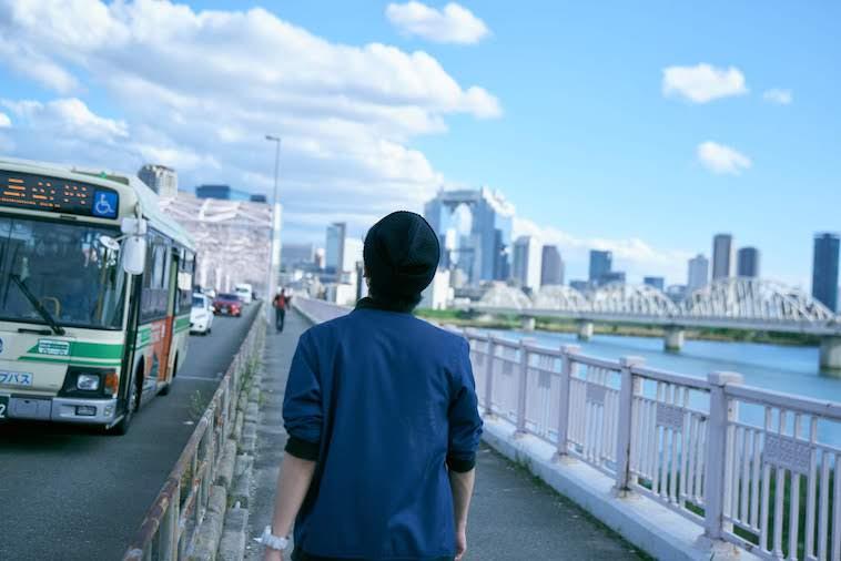 【写真】見渡しの良い橋の上を歩くかないつかさん