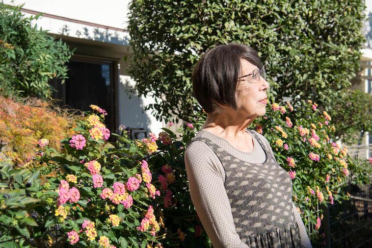 【写真】花壇の前で遠くを見つめるやしろみゆきさん